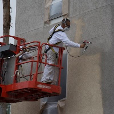 Contractor on a jig-lift spraying a building with Titan RX-Apex gun